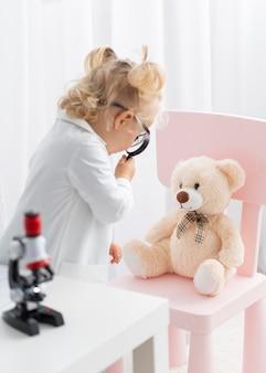 Vista lateral de uma criança bonita com microscópio e lupa
