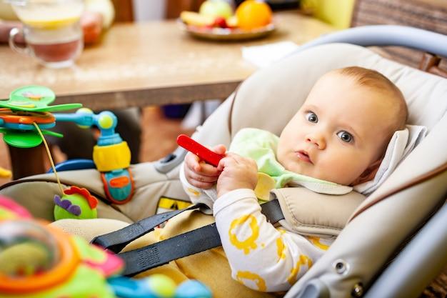 Vista lateral de uma criança esperta, sentada em uma cadeira infantil, mordiscando um brinquedo