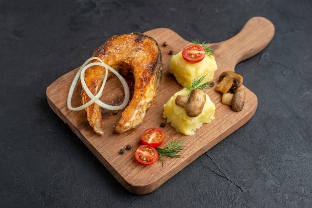 Vista lateral de uma deliciosa farinha de peixe frito e tomates verdes cogumelos em uma tábua de madeira na superfície preta