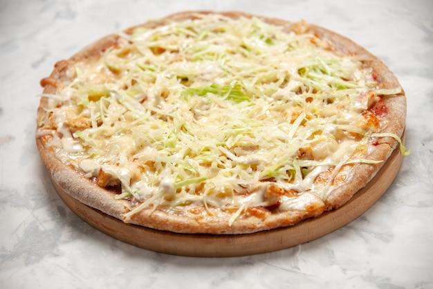Vista lateral de uma deliciosa pizza vegana caseira em uma superfície branca manchada