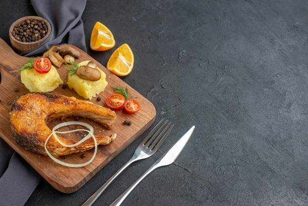Vista lateral de uma deliciosa refeição de peixe frito com cogumelos vegetais queijo na placa de madeira rodelas de limão pimenta em toalha de cor escura talheres em superfície preta afligida