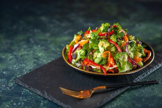 Vista lateral de uma deliciosa salada vegan com ingredientes frescos em um prato e um garfo em uma tábua preta sobre fundo azul