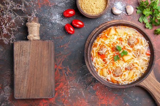 Vista lateral de uma deliciosa sopa de macarrão com frango e uma tábua de corte de madeira, alho, tomates e verduras na mesa escura