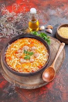 Vista lateral de uma deliciosa sopa de macarrão com frango na tábua de madeira, colher de verduras e garrafa de óleo no fundo escuro