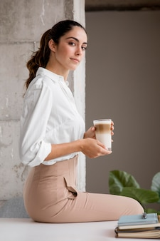 Vista lateral de uma elegante empresária posando com café