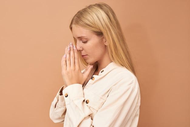 Vista lateral de uma elegante jovem caucasiana com cabelo liso comprido e piercing facial, mantendo as mãos juntas e olhos fechados, rezando