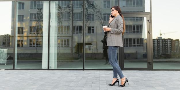 Vista lateral de uma empresária falando ao telefone ao ar livre