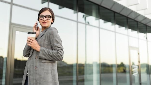 Vista lateral de uma empresária falando ao telefone enquanto toma um café ao ar livre