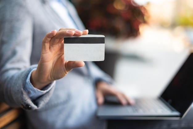 Vista lateral de uma empresária segurando um cartão de crédito enquanto usa o laptop