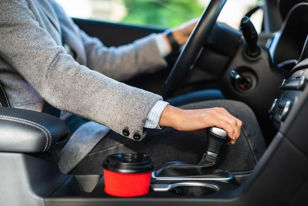 Vista lateral de uma empresária usando o câmbio manual do carro