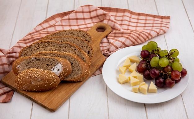 Vista lateral de uma espiga de semente marrom fatiada em uma tábua em tecido xadrez e um prato de queijo e uva em fundo de madeira