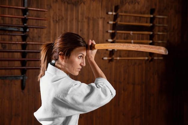 Vista lateral de uma estagiária de artes marciais na sala de prática
