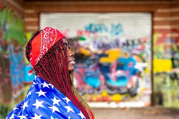 Vista lateral de uma exótica mulher negra com tranças coloridas. coberto com a bandeira dos estados unidos. parede de graffiti