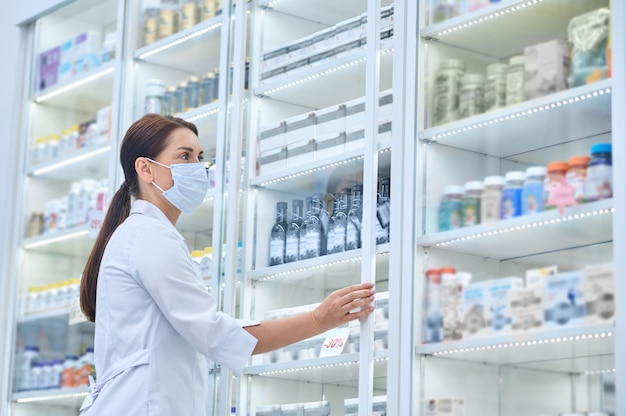 Vista lateral de uma farmacêutica abrindo a porta de vidro da vitrine da farmácia