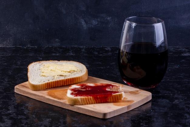 Vista lateral de uma fatia de pão com manteiga com uma fatia de pão com geléia a bordo com um copo de suco