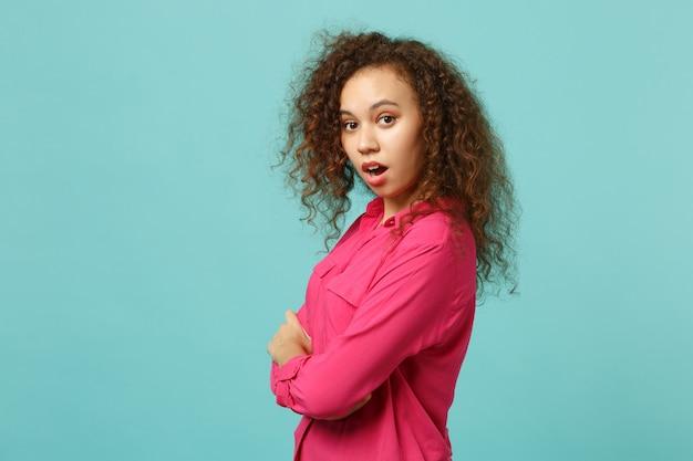 Vista lateral de uma garota africana chocada em roupas casuais rosa, olhando a câmera de mãos cruzadas, isoladas no fundo da parede azul turquesa. conceito de estilo de vida de emoções sinceras de pessoas. simule o espaço da cópia.