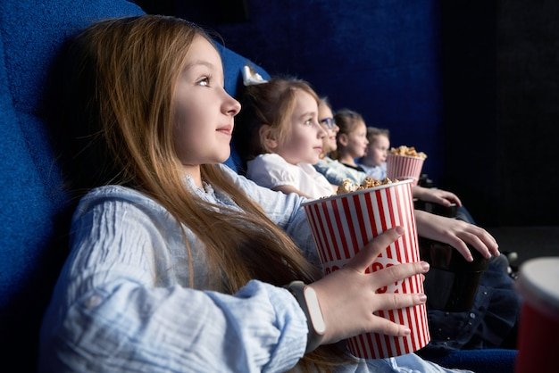 Vista lateral de uma garota bonita assistindo filme no cinema