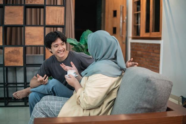 Vista lateral de uma garota com um véu e um homem conversando na sala de estar sentado em uma cadeira de madeira