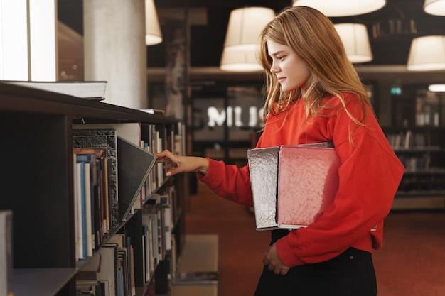Vista lateral de uma garota ruiva, estudante universitária escolhe um livro da prateleira da biblioteca ou livraria.