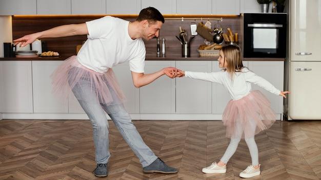 Vista lateral de uma garota se divertindo com o pai em saias tutu