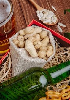 Vista lateral de uma garrafa de cerveja com amendoins em um saco em uma caixa com palha e uma caneca de cerveja no rústico