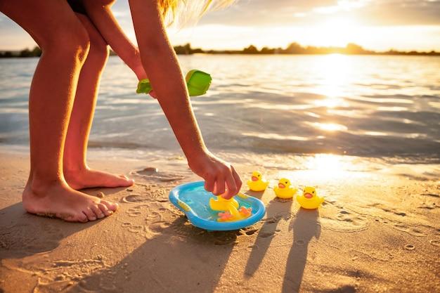 Vista lateral de uma irreconhecível garota caucasiana brincando com patos amarelos de borracha em uma pequena piscina azul