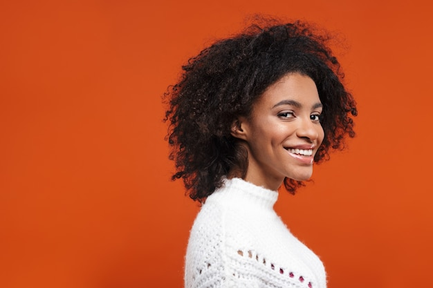 Vista lateral de uma jovem africana bonita e alegre, vestindo uma camisola em pé sobre a parede vermelha