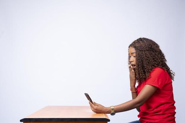Vista lateral de uma jovem animada usando seu telefone parecendo surpresa.