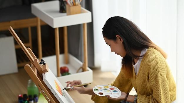 Vista lateral de uma jovem artista com uma paleta na mão desenhando a imagem em seu estúdio.