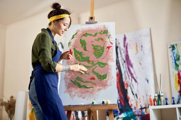 Vista lateral de uma jovem artista feminina de avental, pintando um quadro no cavalete, aplicando tinta na tela com