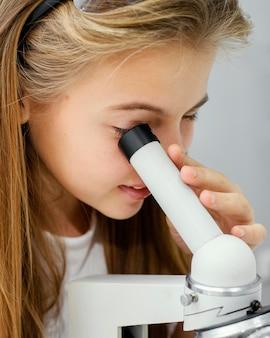 Vista lateral de uma jovem cientista olhando através do microscópio