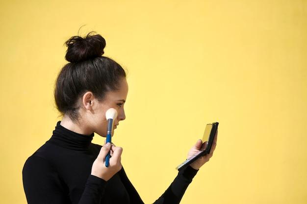 Vista lateral de uma jovem com rabo de cavalo usando o telefone como espelho enquanto aplica o pincel de maquiagem na pele do rosto