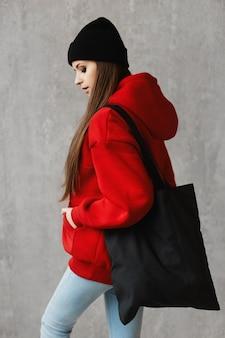 Vista lateral de uma jovem com um capuz vermelho e chapéu preto com uma bolsa grande no ombro