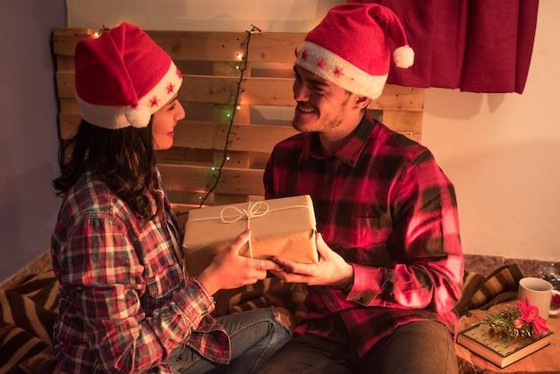 Vista lateral de uma jovem dando uma caixa de presente de natal para o namorado em um ambiente rústico