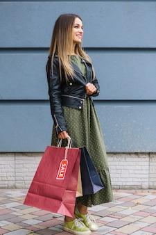 Vista lateral de uma jovem elegante, vestindo jaqueta segurando sacolas de compras na mão