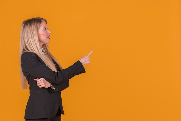 Vista lateral de uma jovem empresária apontando o dedo contra o pano de fundo