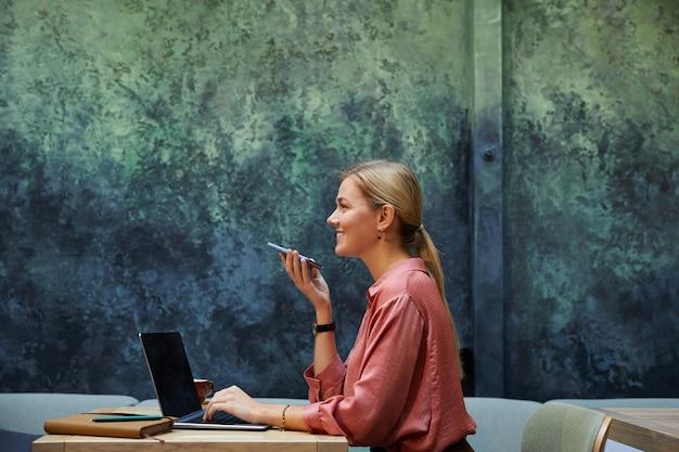Vista lateral de uma jovem empresária gravando uma mensagem no celular durante seu trabalho à mesa de um café