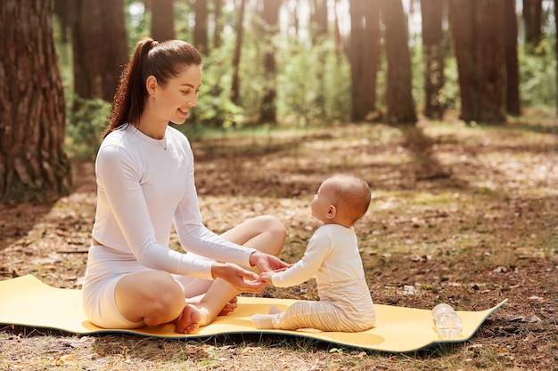 Vista lateral de uma jovem feliz e alegre mãe sentada no karemat na floresta com seu bebê