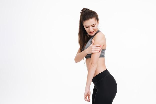 Vista lateral de uma jovem fitness com dor, segurando o braço dela e olhando para longe, isolada