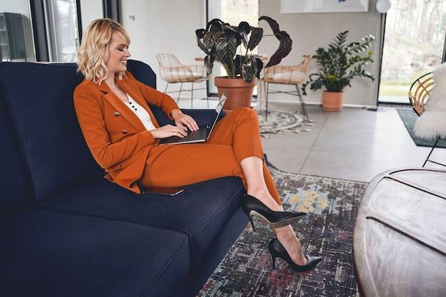 Vista lateral de uma jovem freelancer satisfeita digitando em seu laptop no sofá