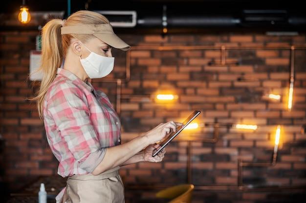 Vista lateral de uma jovem garçonete linda em um uniforme moderno e uma máscara protetora no rosto, usando um tablet digital para pedir comidas e bebidas