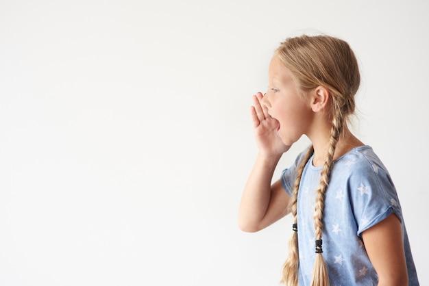 Vista lateral de uma jovem gritando
