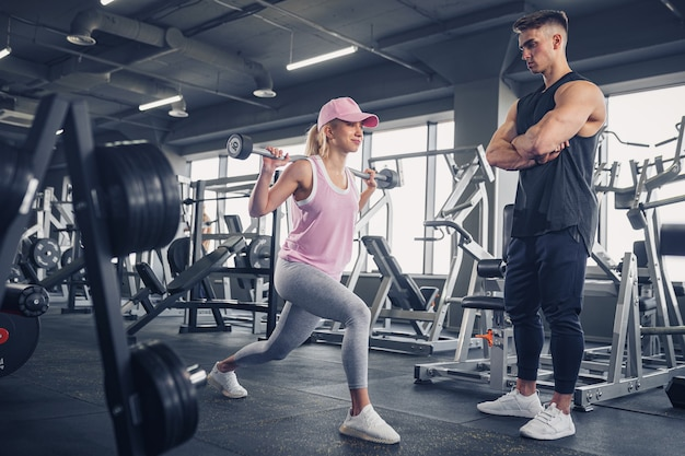 Vista lateral de uma jovem loira esportiva, focada e motivada, em roupas esportivas, fazendo exercícios para as pernas, enquanto um belo treinador pessoal musculoso a monitora no ginásio