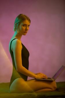 Vista lateral de uma jovem loira séria com o laptop sobre os joelhos, olhando para você enquanto faz networking na cama pela manhã