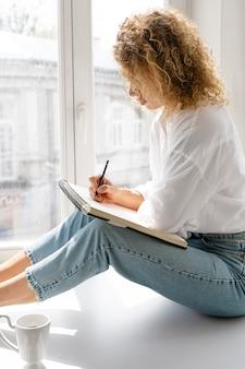 Vista lateral de uma jovem mulher desenhando em casa perto da janela