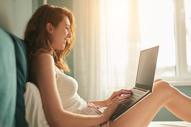Vista lateral de uma jovem mulher em pijamas sorrindo e navegando no netbook enquanto descansava na cama pela manhã em casa