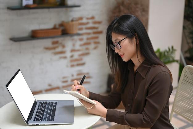 Vista lateral de uma jovem mulher trabalhando com agenda e laptop na mesa redonda no café