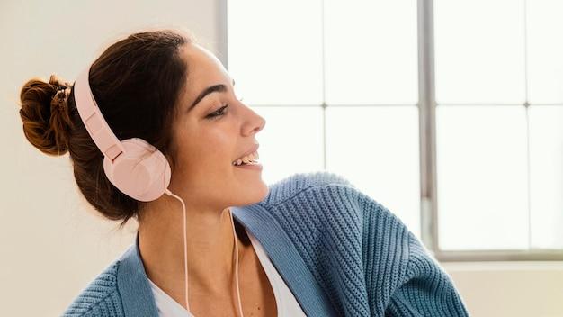 Vista lateral de uma jovem ouvindo música em fones de ouvido