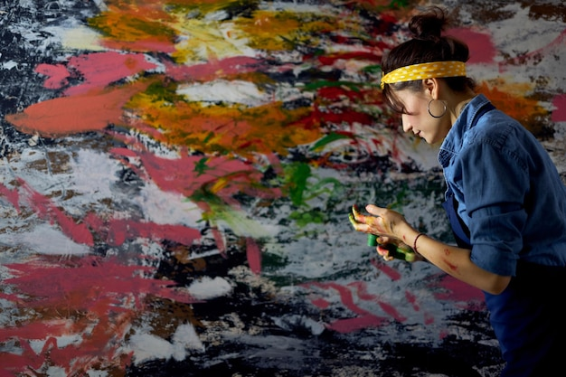Vista lateral de uma jovem pintora criando uma grande e moderna pintura a óleo abstrata com tinta