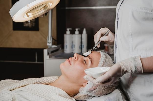 Vista lateral de uma jovem recebendo um tratamento para a pele do rosto no spa